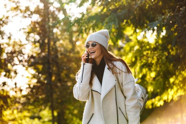 Bella giovane donna vestita in cappotto di autunno e cappello camminando all'aperto, parlando al cellulare, ridendo