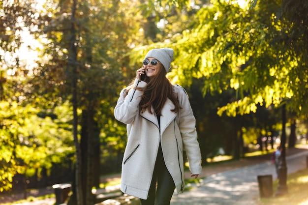 Bella giovane donna vestita in cappotto di autunno e cappello che cammina all'aperto, parlando al telefono cellulare