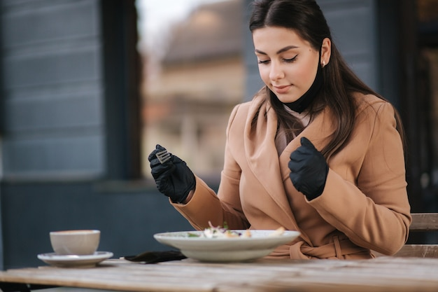 Bella giovane donna che mangia pranzo nella caffetteria all'aperto sulla terrazza. femmina in maschera protettiva nera.