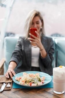 Bella giovane donna mangia e scatta foto cibo in un ristorante