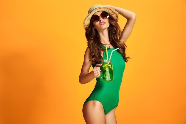 Bella giovane donna in costume da bagno color smeraldo e cappello di paglia che tiene la brocca con la bevanda fredda mentre levandosi in piedi sulla parete gialla