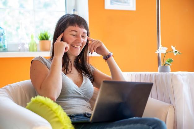 Bella giovane donna che guarda emotivamente il computer portatile. emotivamente sorpreso e piange per il successo.