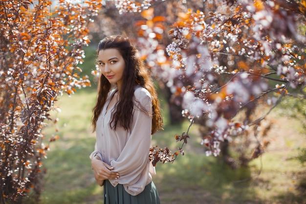 Bella giovane donna che gode di una soleggiata giornata di primavera in un parco durante la stagione della fioritura dei ciliegi. elegante