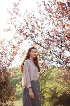 Bella giovane donna che gode di una soleggiata giornata di primavera in un parco durante la stagione della fioritura dei ciliegi