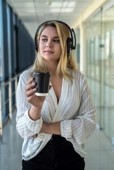 La bella giovane donna gode del caffè e ascolta la musica durante la pausa pranzo nel corridoio di un moderno centro commerciale