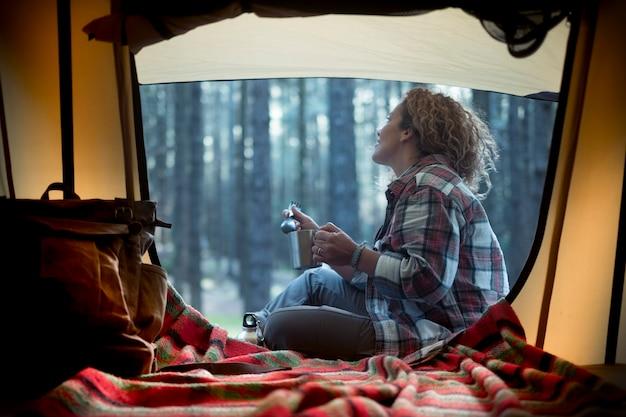 La bella giovane donna gode della natura della foresta all'ingresso della sua tenda nel bosco