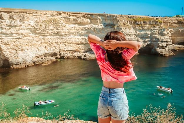 Una bella giovane donna gode di un pittoresco paesaggio marino con acque azzurre sulla costa occidentale della crimea