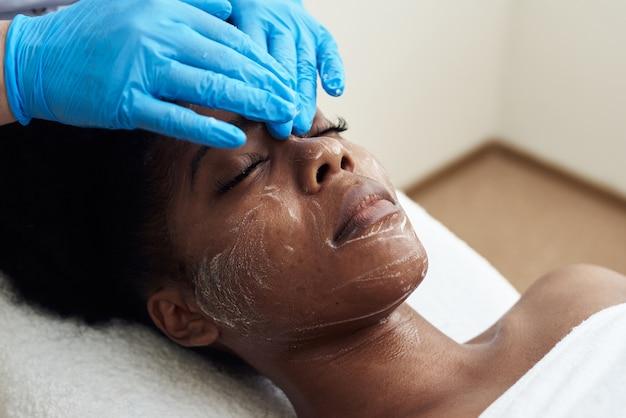 Una bella giovane donna gode di un massaggio viso tonificante. il concetto di cure termali, cura della pelle