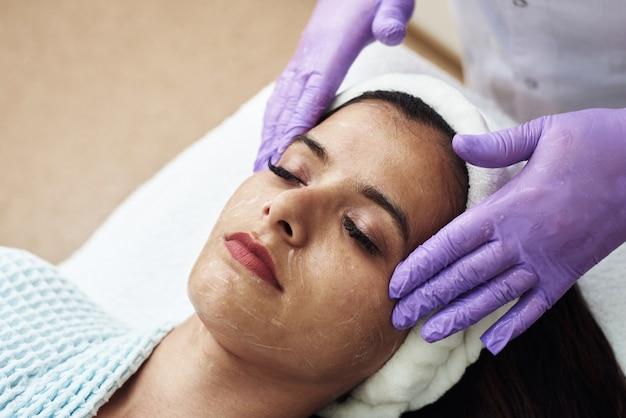 Una bella giovane donna gode di un massaggio viso tonificante. il concetto di cure termali