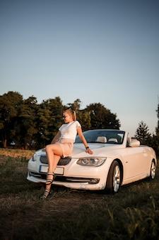 Una bella giovane donna dall'aspetto europeo sul viso degli occhiali da sole, sta vicino alla sua decappottabile bianca. imprenditrice di successo donna e la sua auto bianca.