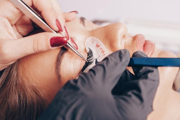 Bella giovane donna alla procedura di estensione delle ciglia. i cosmetici e la cura del corpo si chiudono sul colpo.