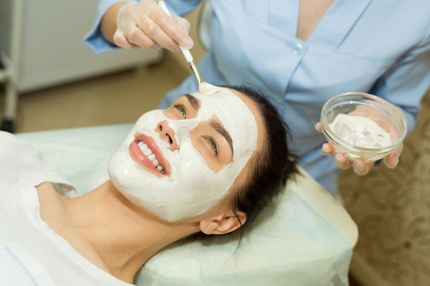 Bella giovane donna su un trattamento viso in un salone di bellezza che applica una crema