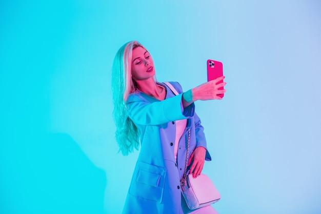Bella giovane donna in abiti alla moda con una borsa elegante fa una foto selfie su uno smartphone con luce rosa neon in studio