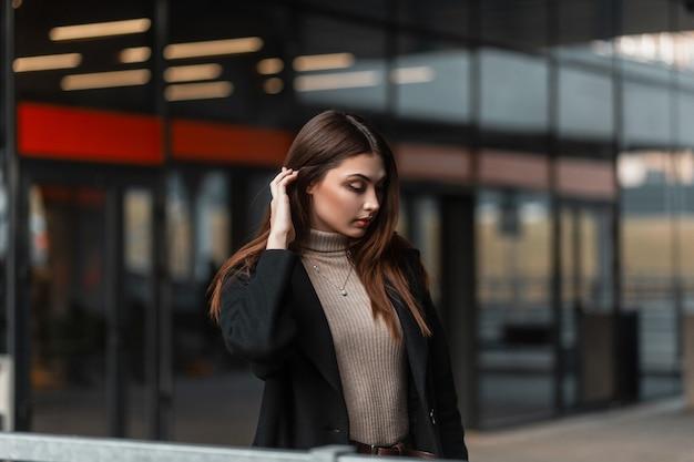 La bella modella di moda giovane donna in abbigliamento alla moda raddrizza i capelli chic all'aperto in una giornata primaverile. elegante ragazza europea in un elegante cappotto nero posa vicino a un edificio di vetro in strada. signora carina.