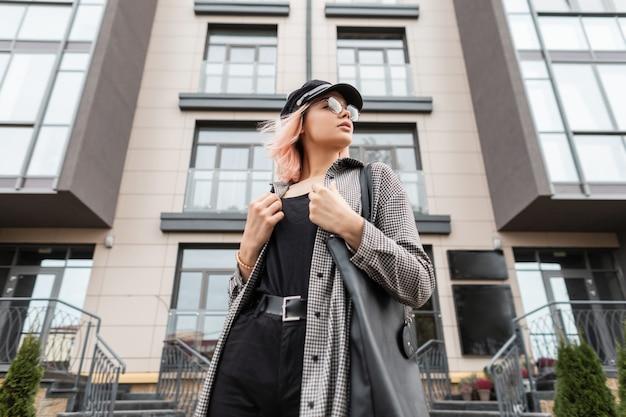 Bella giovane donna in abiti alla moda con berretto, borsa e occhiali si erge sullo sfondo di un edificio residenziale vintage