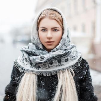 Bella giovane donna in una sciarpa alla moda in una giornata invernale