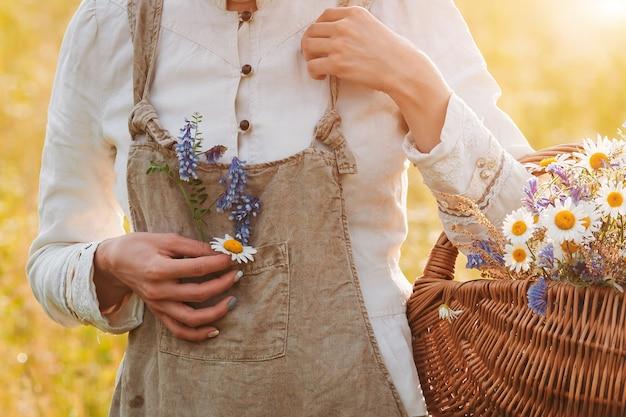 La bella giovane donna in un campo di fiori gode del profumo e della vista delle margherite di campo