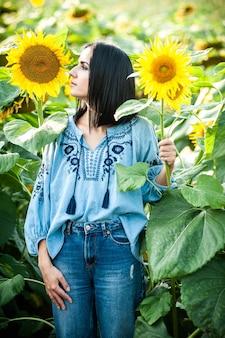Bella giovane donna in un campo di girasoli