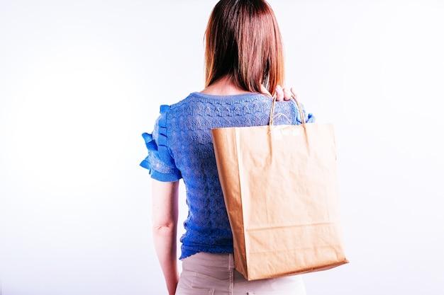 Bella giovane donna da dietro con un sacchetto di carta dietro la schiena. concetto di acquisto sostenibile. senza plastica