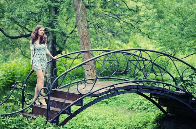 Bella giovane donna in giardino sul ponte