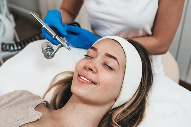 Bella giovane donna che ottiene un trattamento di mesoterapia al salone di bellezza cosmetica.