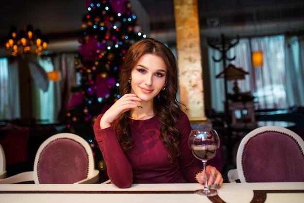 Bella giovane donna in abito grigio sta con un bicchiere di vino in mano su sfondo di albero di natale, luci e ghirlande.