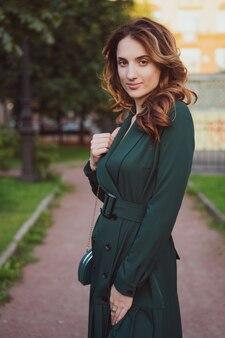 Bella giovane donna in abito verde all'aperto sorridente