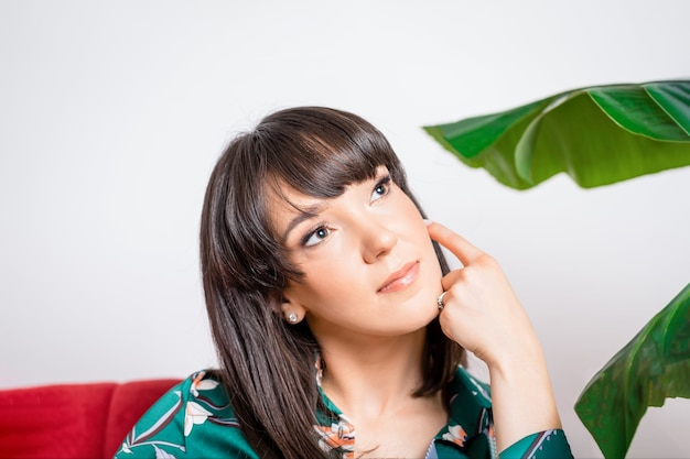Bella giovane donna e foglie verdi di ficus