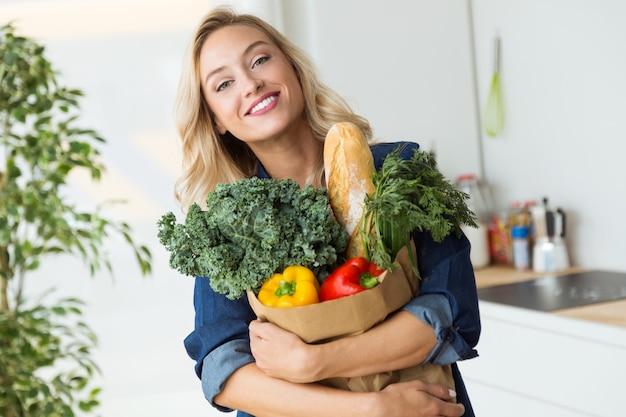 Bella borsa della spesa della drogheria della giovane donna con le verdure a casa.