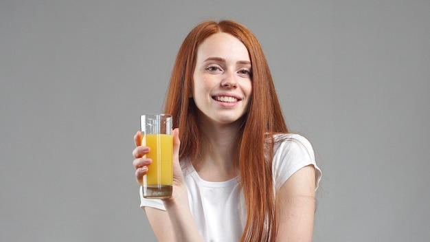 Bella giovane donna felice e bere succo d'arancia. giovane donna con un bicchiere di succo d'arancia