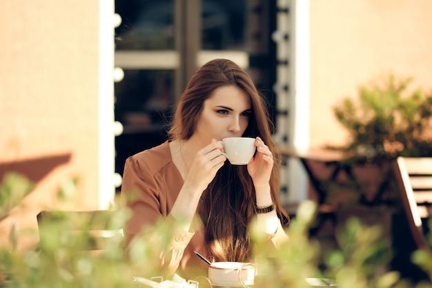 La bella giovane donna ha pausa caffè nel bel mezzo della giornata di sole