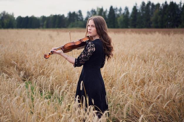 Una bellissima giovane donna ha smesso di suonare il violino e guarda altrove