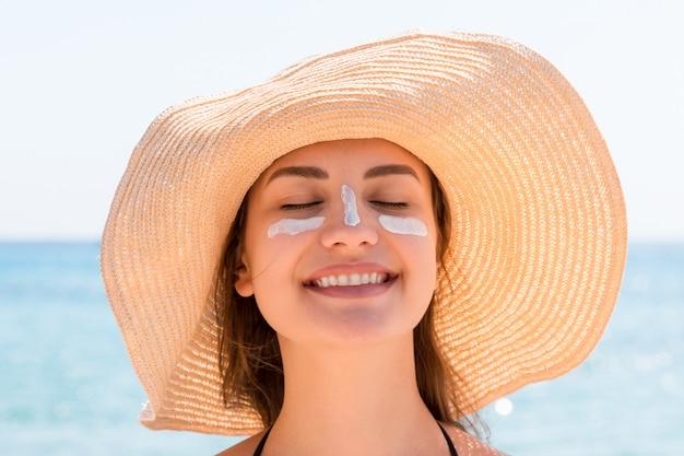 Bellissima giovane donna con cappello sta applicando crema solare sotto gli occhi e sul naso come un indiano. concetto di protezione solare