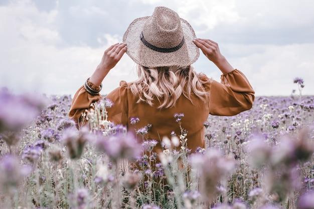 Bella giovane donna in cappello in campo di lavanda. fiori che sbocciano