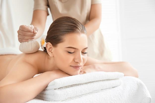 Bella giovane donna con massaggio alla schiena con sacchetti di erbe