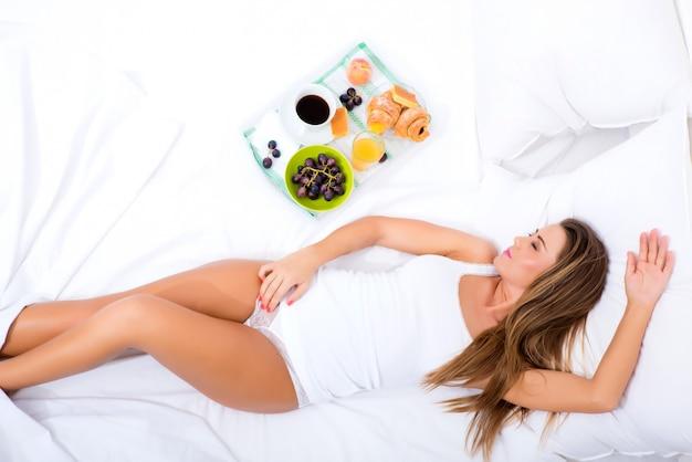 Una bellissima giovane donna fare colazione a letto