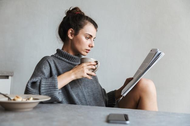 Bella giovane donna con una sana colazione seduti su una cucina, leggendo la rivista