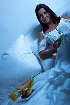 Bella giovane donna che mangia il suo primo caffè a letto