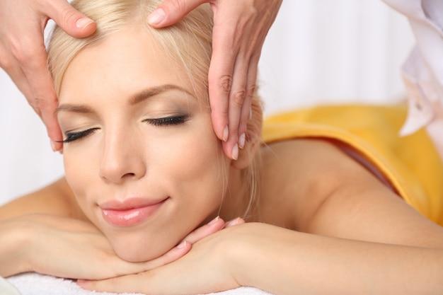 Bella giovane donna che ha massaggio nel salone della stazione termale