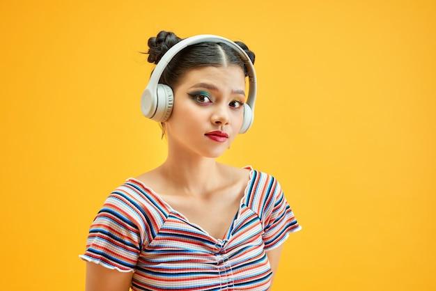 Bella giovane donna in cuffia che ascolta musica su sfondo colorato