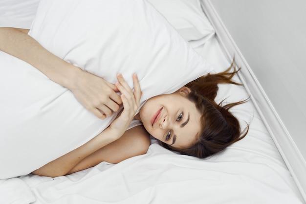 La bella giovane donna nel suo bellissimo letto bianco come la neve rilassa e rilassa, bella prova