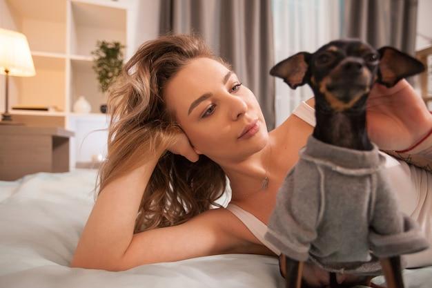 Bella giovane donna nel suo comodo pigiama che riposa a letto con il suo cagnolino.