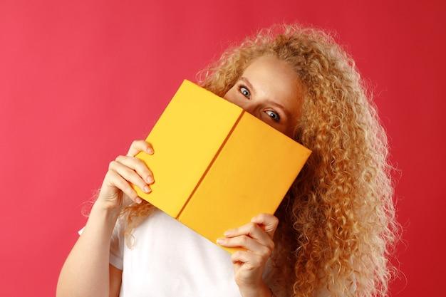 Bella giovane donna che si nasconde dietro il libro contro il rosa