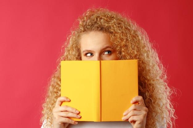 Bella giovane donna che si nasconde dietro il libro contro il rosso