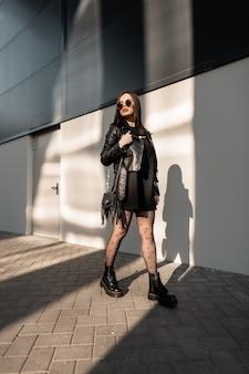 Bella giovane donna hipster in abiti alla moda in pelle nera con occhiali da sole alla moda e stivali cammina per strada vicino a un edificio moderno alla luce del sole