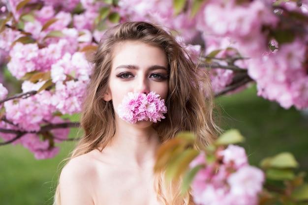 Bella giovane donna tenere fiori rosa in bocca ragazza di bellezza sulla fioritura sakura sboccia fiori sulla superficie della natura