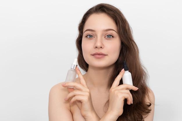 Bella giovane donna con bottiglie di collagene e siero idratante.