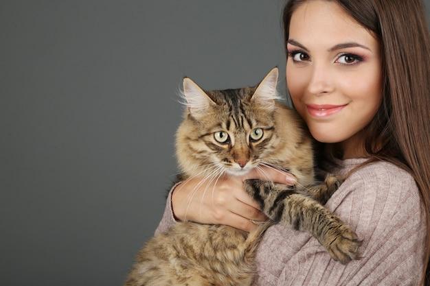 Bella giovane donna che tiene gatto su sfondo grigio
