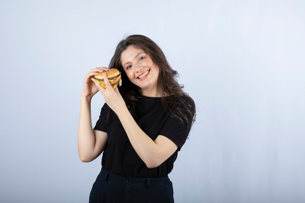 Bella giovane donna che tiene delizioso hamburger di manzo.
