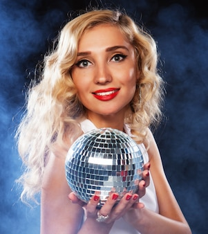 Bella giovane donna che tiene la palla da discoteca al night club